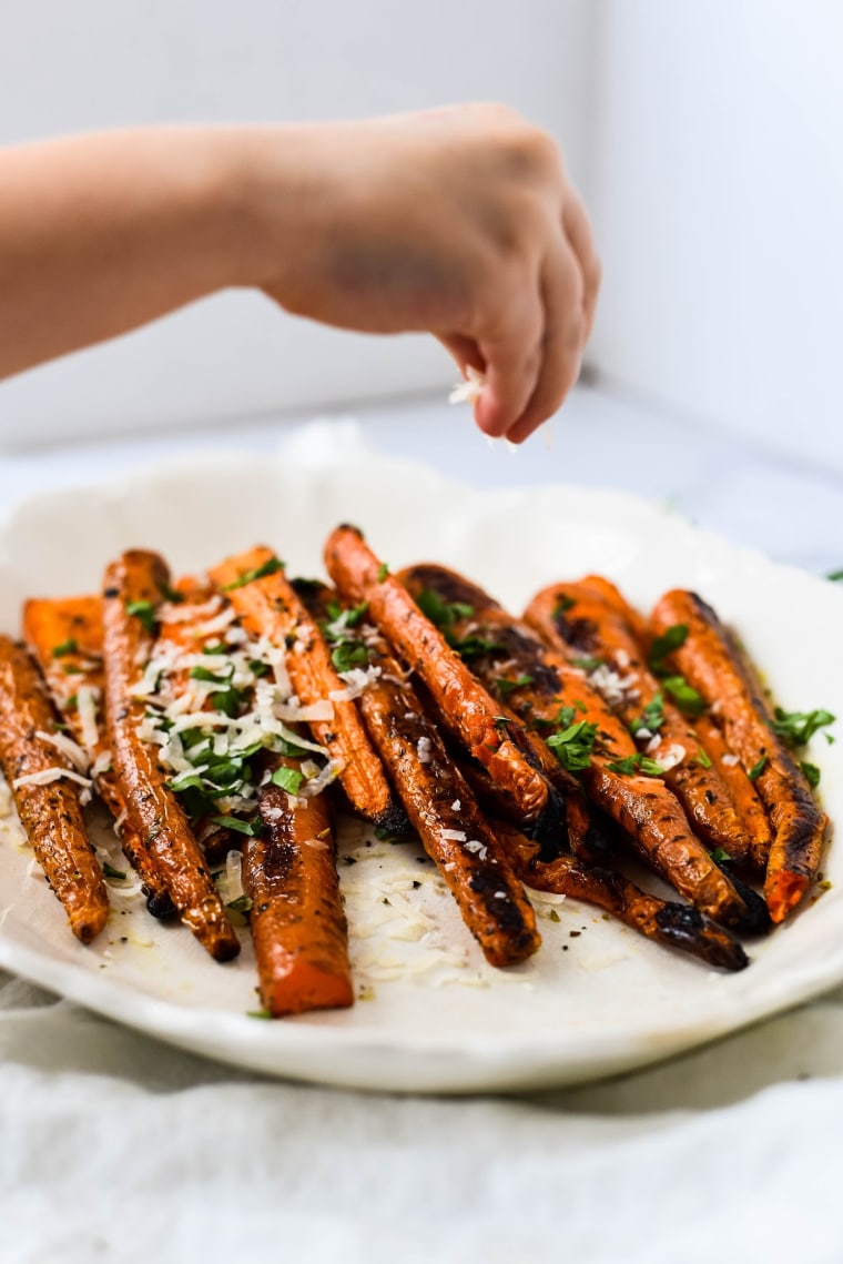 hand sprinkling grated parmesan on roasted carrot recipe