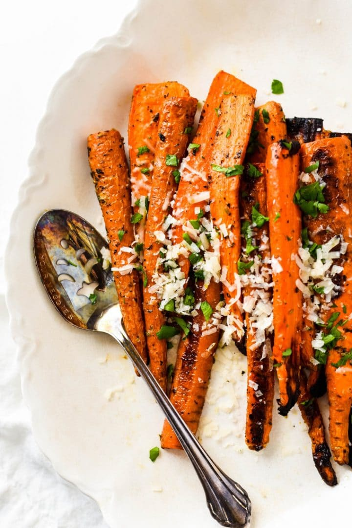 close up of italian herb roasted carrots on white platter with spoon