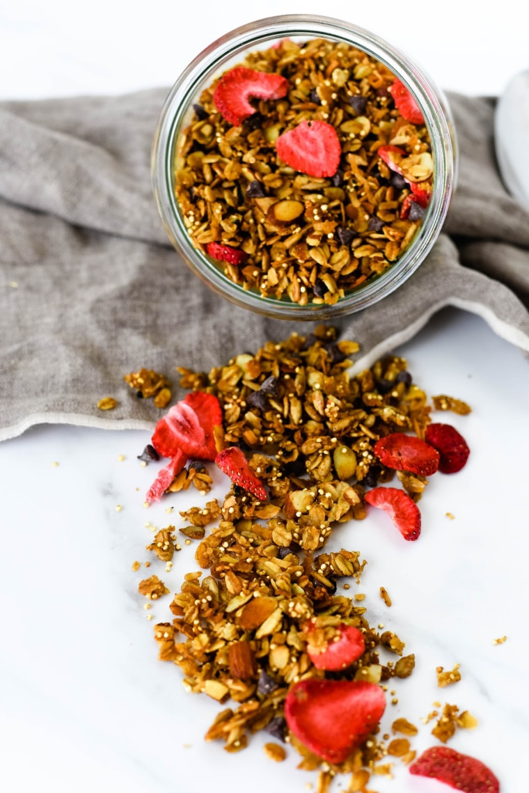 homemade granola with dried strawberries spilling out of jar