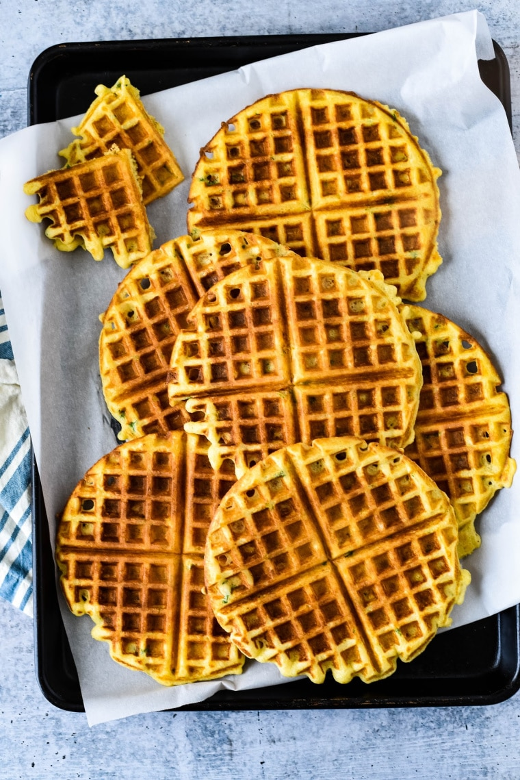 savory waffles stacked on baking sheet with parchment paper