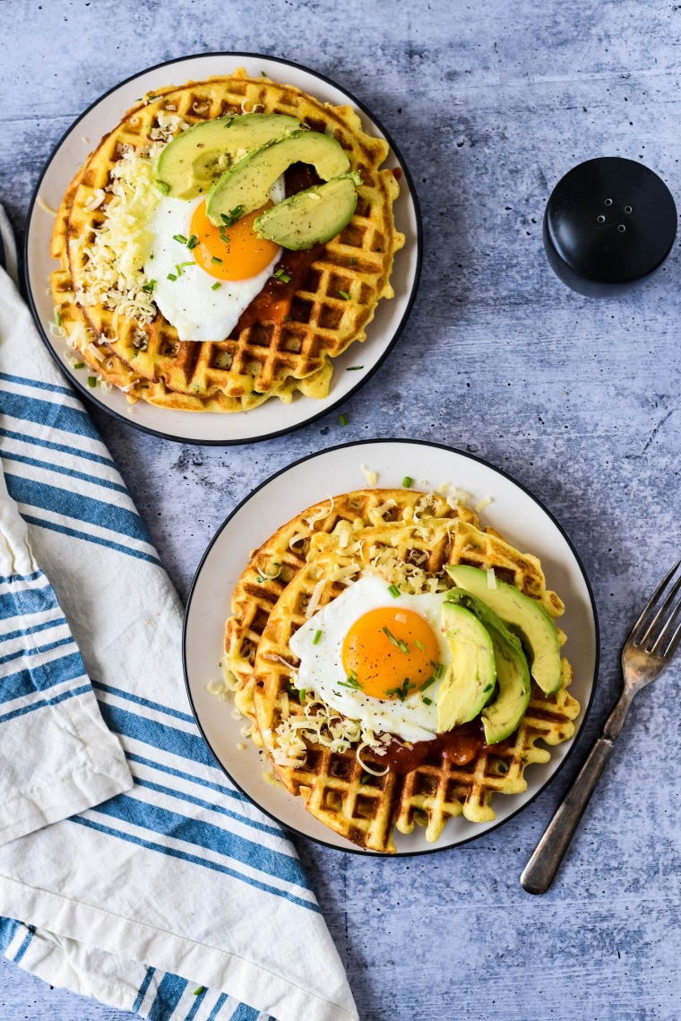 savory waffles topped with fried eggs and avocados