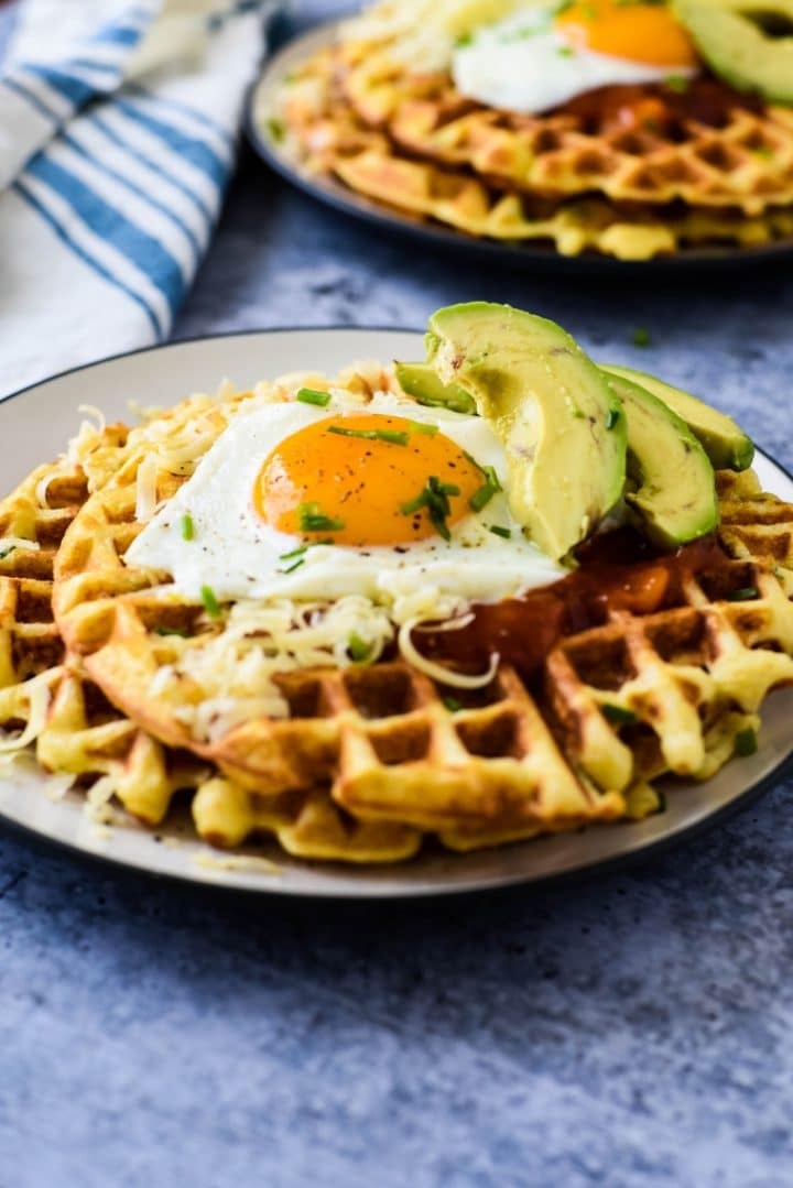 cornmeal waffles on a plate with eggs and avocado slices
