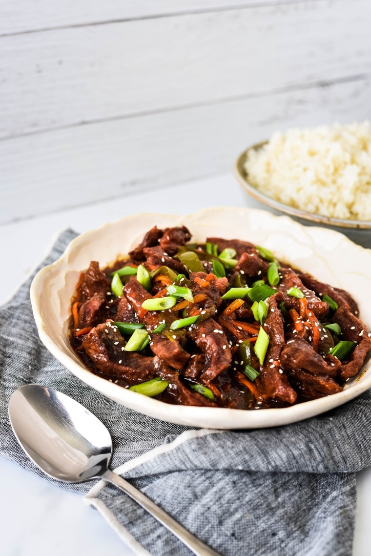 Bowl of Slow Cooker Mongolian Beef with rice in background