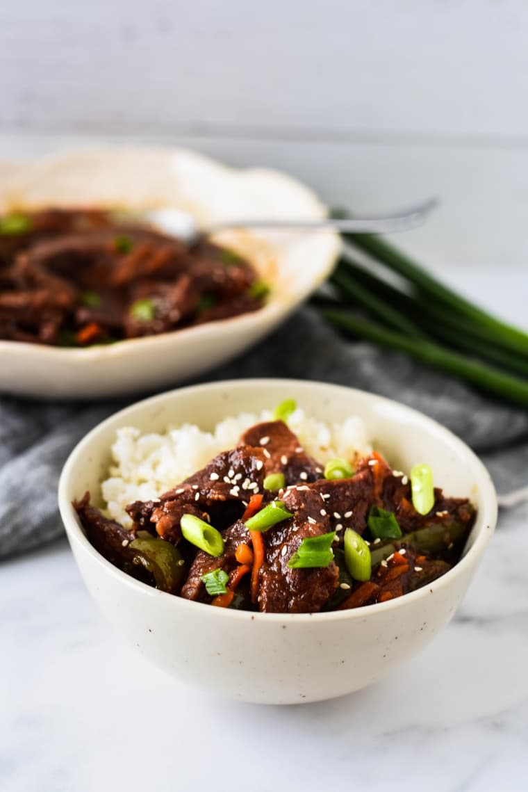 bowl with mongolian beef and rice with serving bowl in background