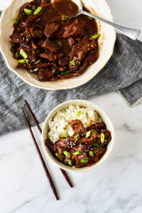 bowl of mongolian beef with rice next to serving bowl