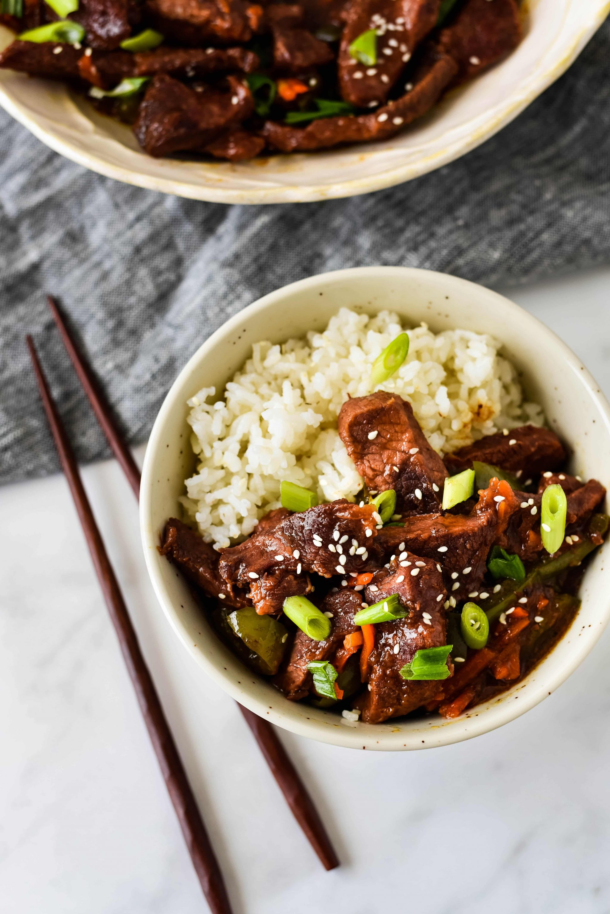 Bowl of Slow Cooker Mongolian Beef with Rice and chopsticks