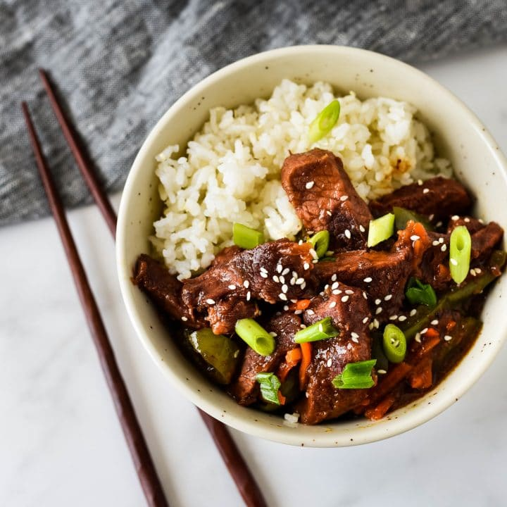 slow cooker mongolian beef in bowl with rice and chopsticks