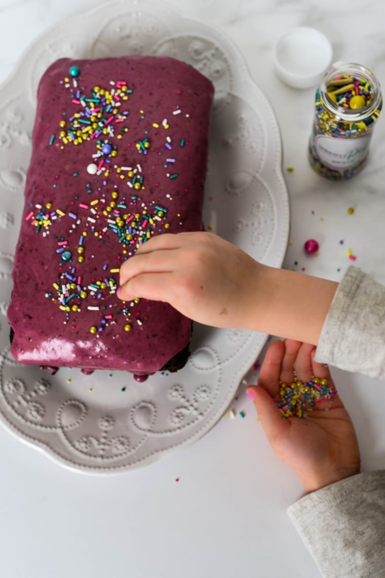 placing sprinkles on chocolate wacky cake
