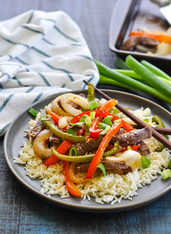 chinese pepper steak recipe with rice on gray plate