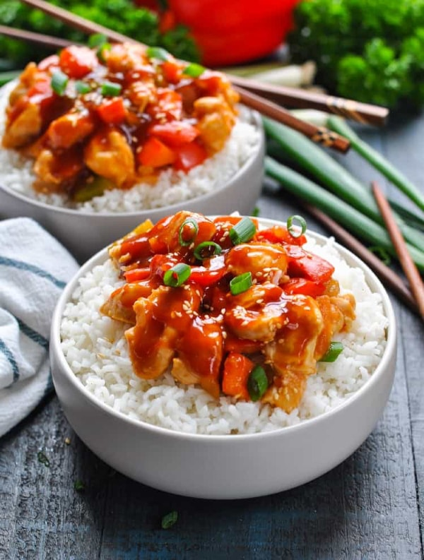 sweet and sour chicken recipe on rice in white bowls