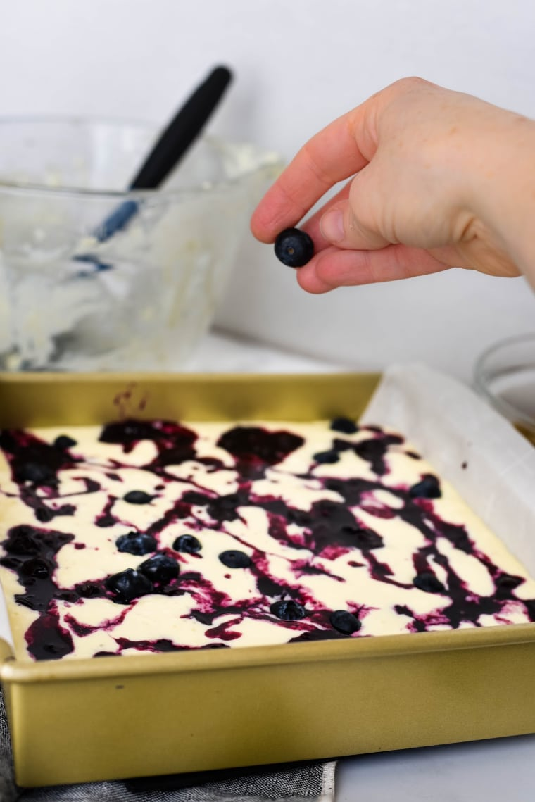 adding blueberry syrup to cheesecake bars