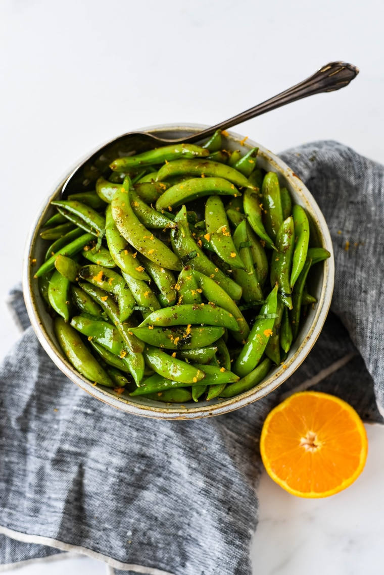 sugar snap peas in bowl with orange and mint