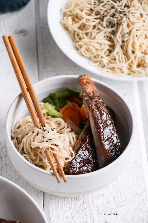 asian ribs with noodles in bowl with chopsticks