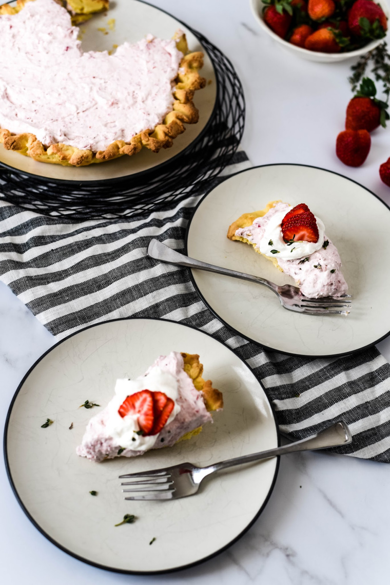 Two slices of Strawberry Mousse Tart on plates with pie behind