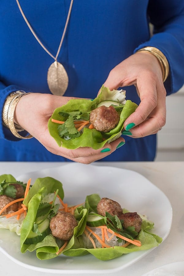 asian meatballs in lettuce wraps held by hand