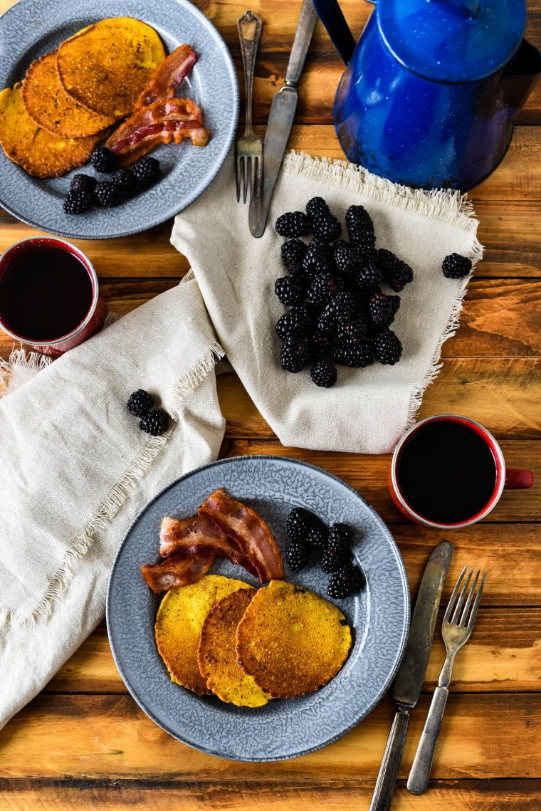 corn cakes on tin plates with bacon and blackberries