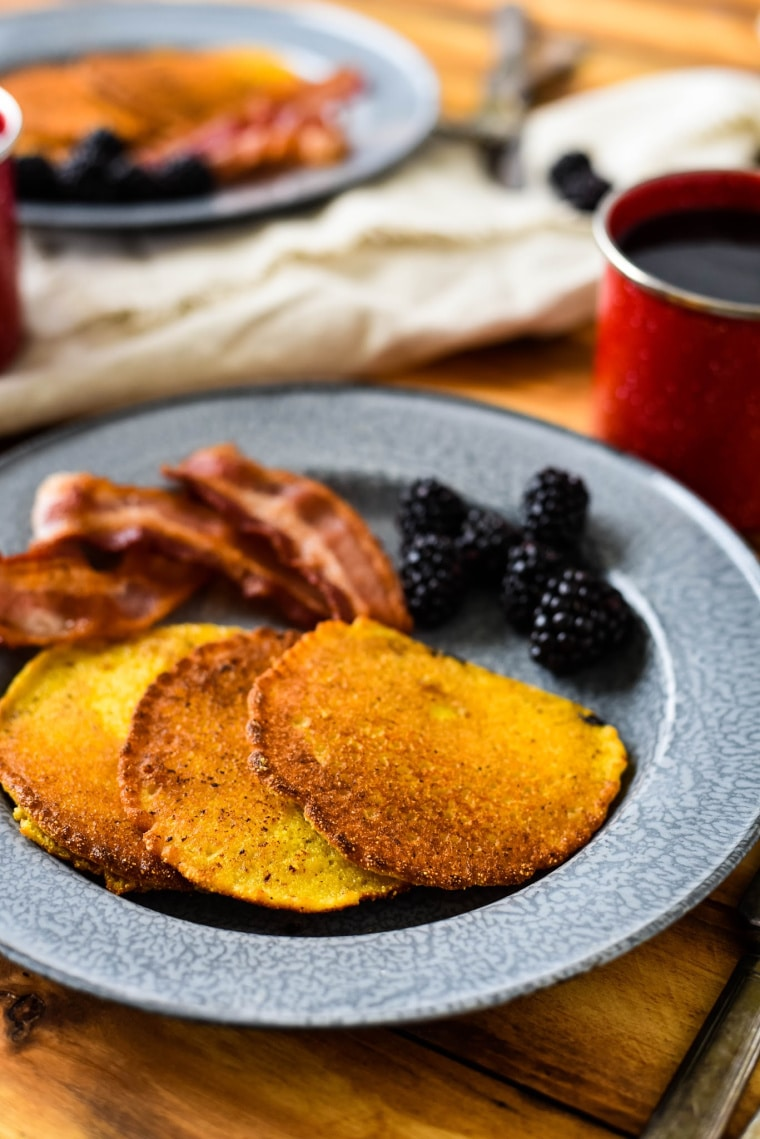 corn cakes on tin plate with bacon and blackberries