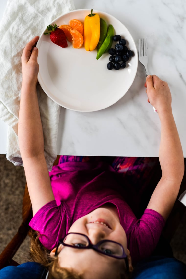 kid smiling with plate of food