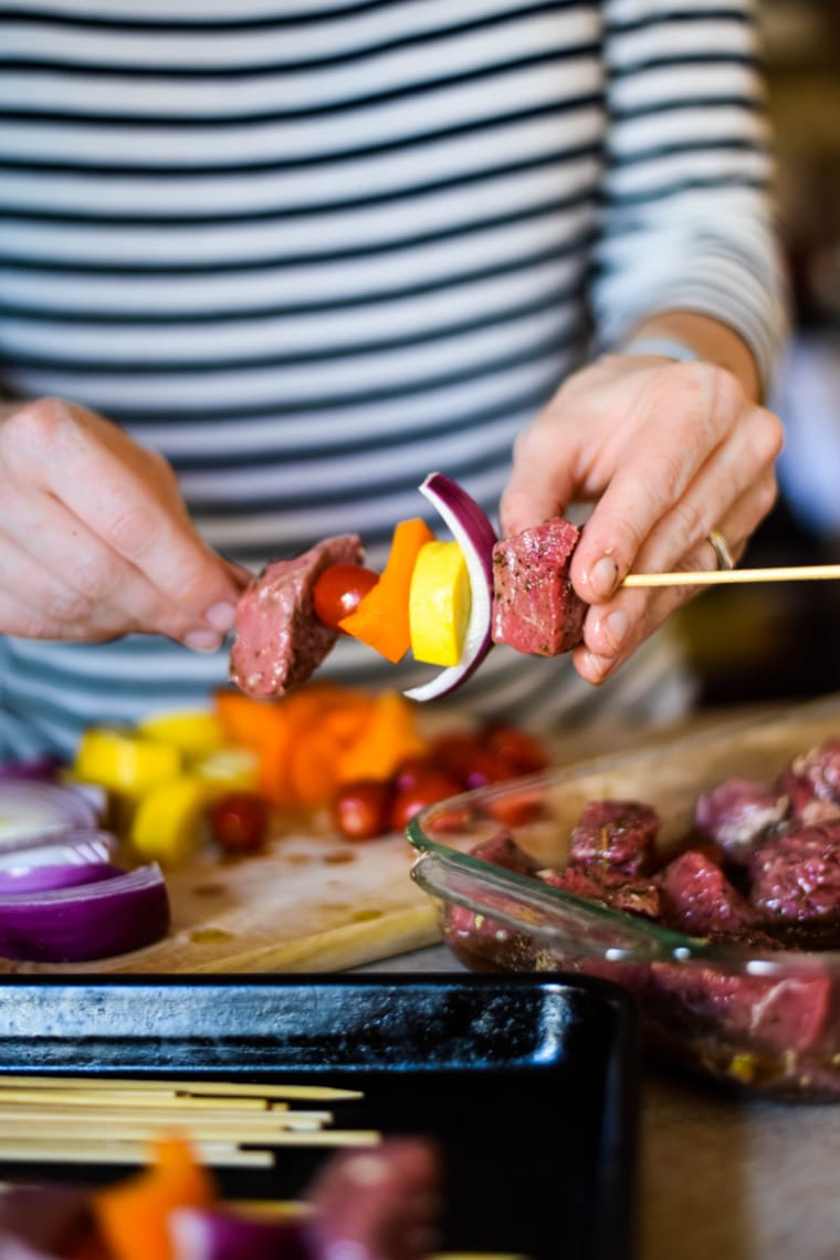adding ingredients to skewers of za'atar beef kabobs