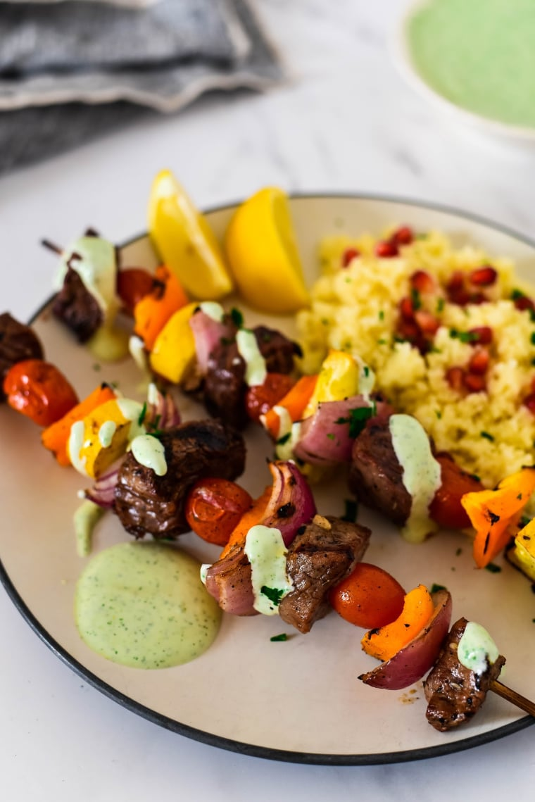 two skewers with za'atar beef and vegetables next to couscous on plate