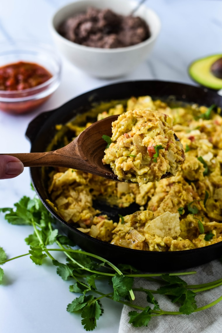 wooden spoon with migas and cast iron skillet