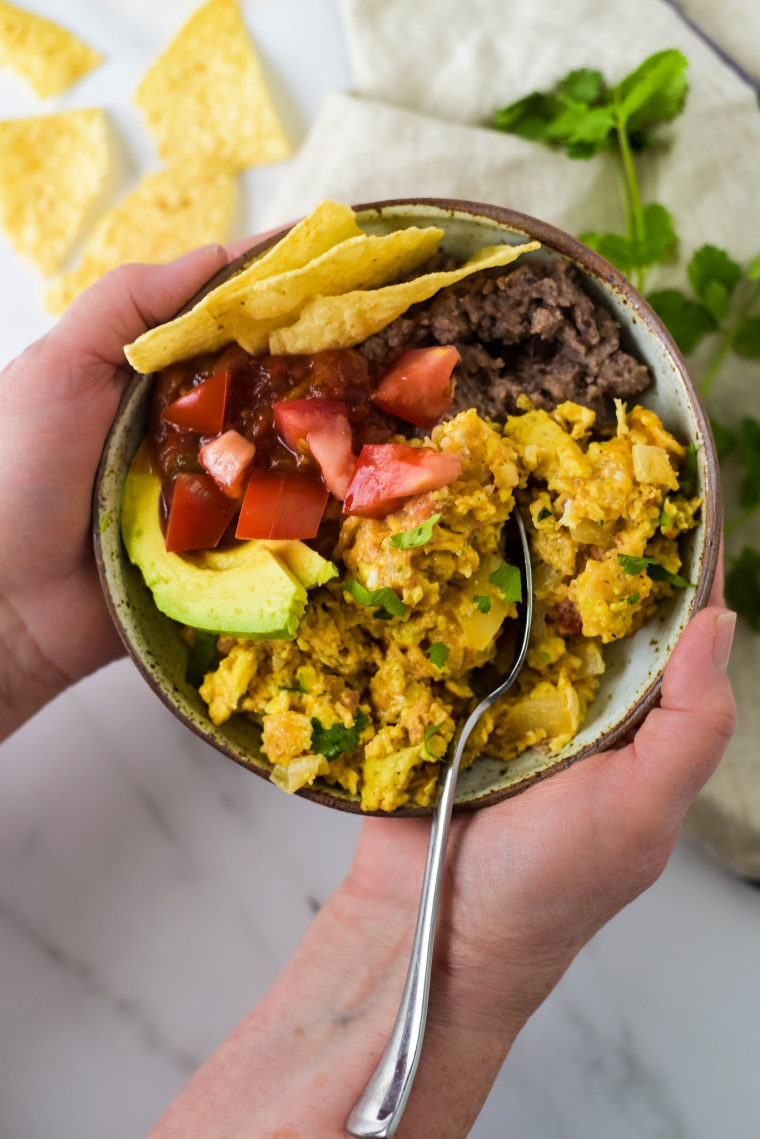 tex mex migas in bowl being held in hands
