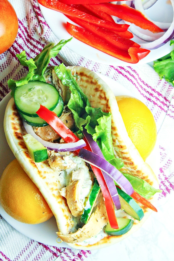 Slow-Cooker-Greek-Chicken-Gyros on table with fresh produce besides