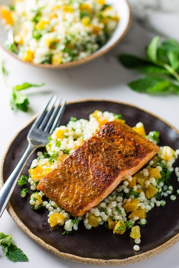 piece of salmon on couscous with orange slices