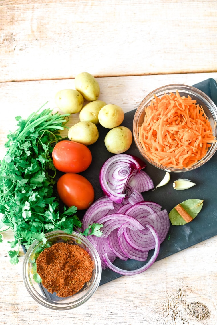 ingredients for beef pilau - carrots, onions, tomatoes, potatoes, spices, and cilantro