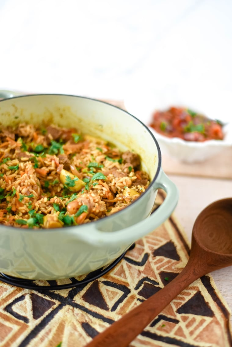 enameled cast iron pan with beef pilau, wooden serving spoon beside