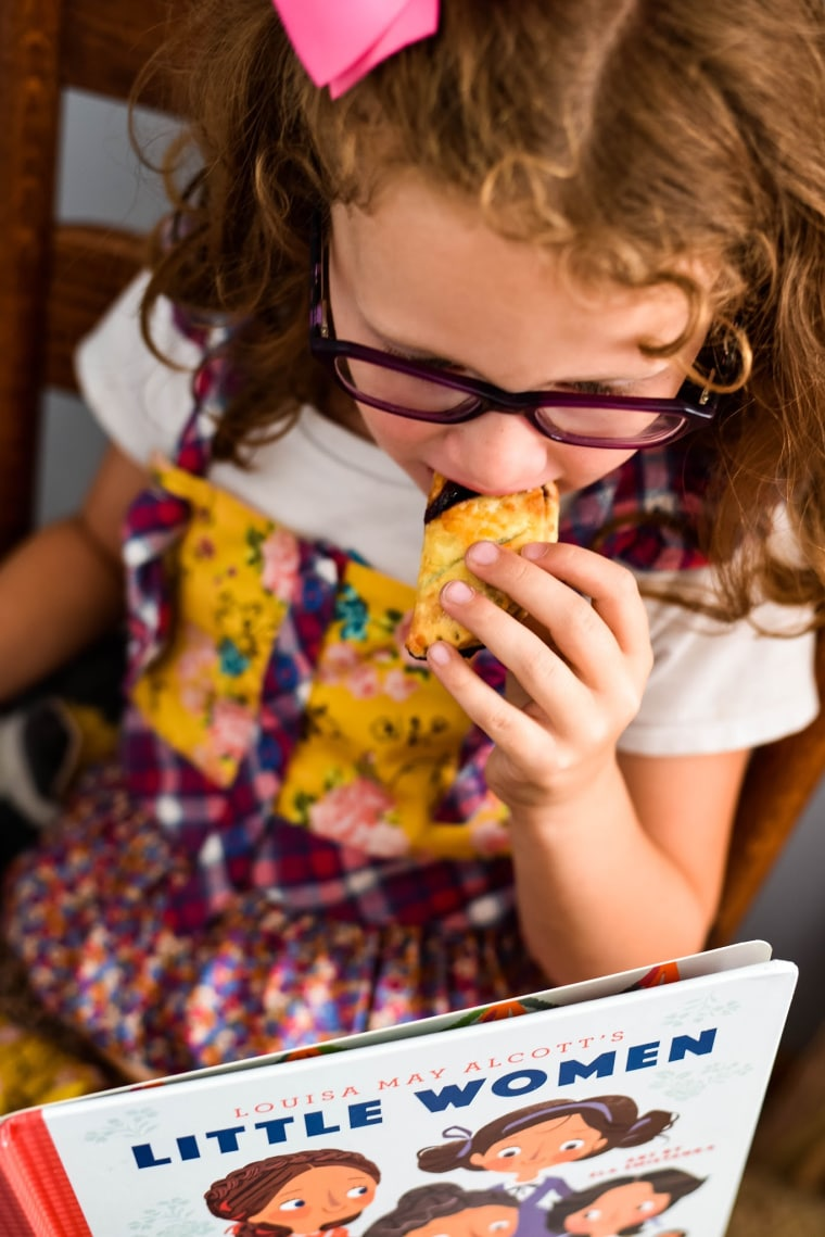 girl eating turnover and reading little women book