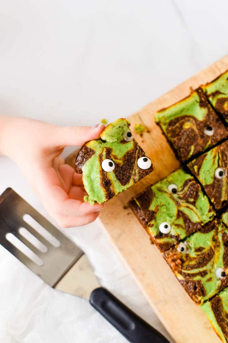 child hand taking halloween brownie off of serving board