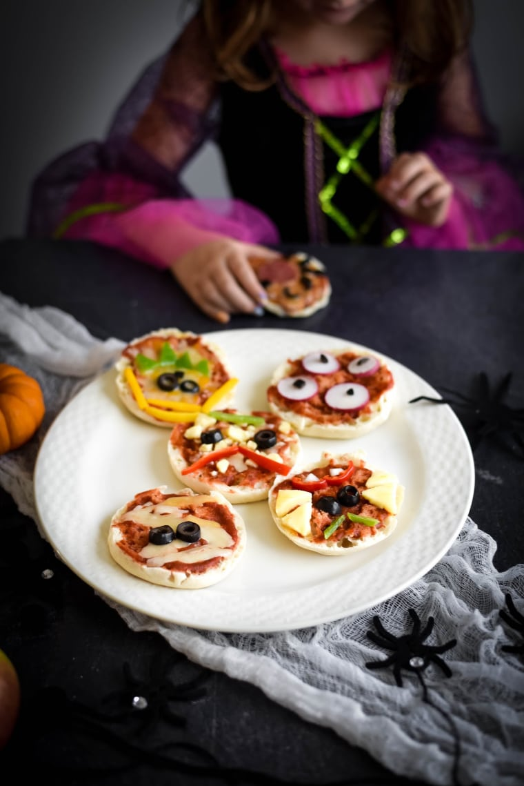 little girl dressed as with with plate of halloween pizzas