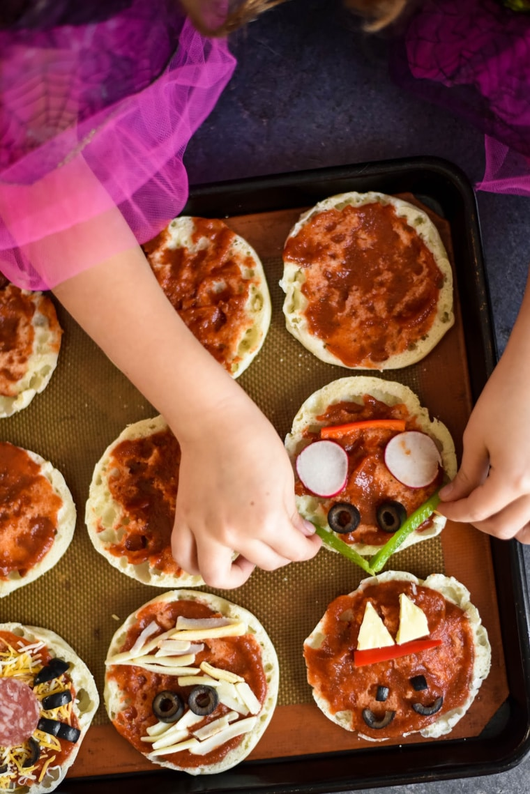 little girl using vegetables to make halloween pizzas