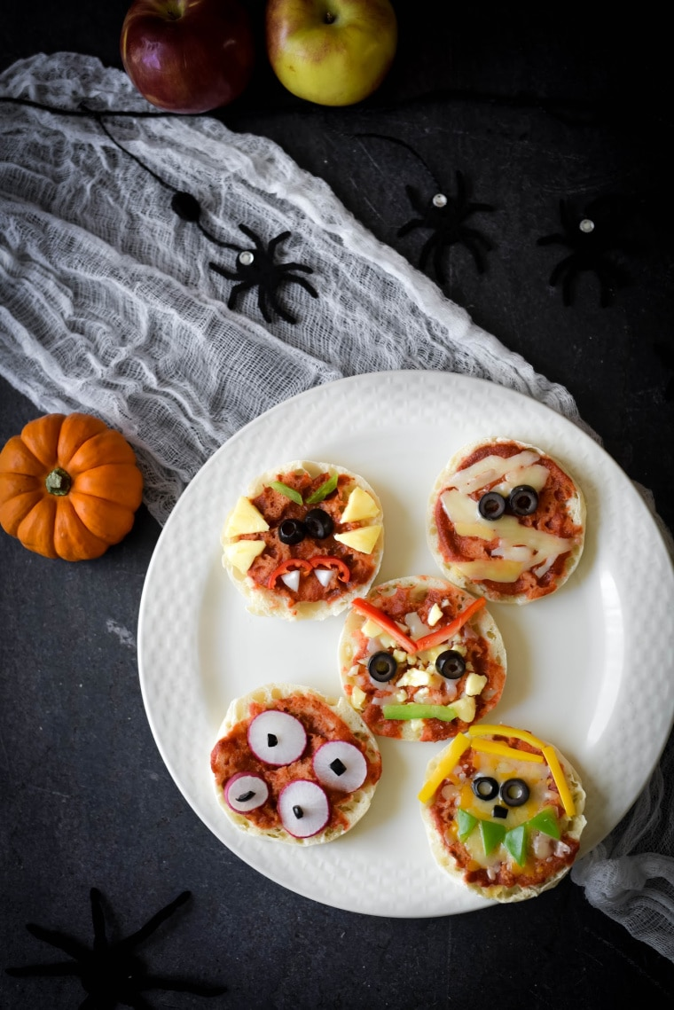 white plate with halloween decorations and mini pizzas