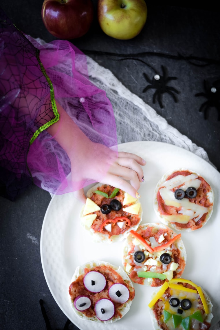 girl taking halloween pizza off of white plate