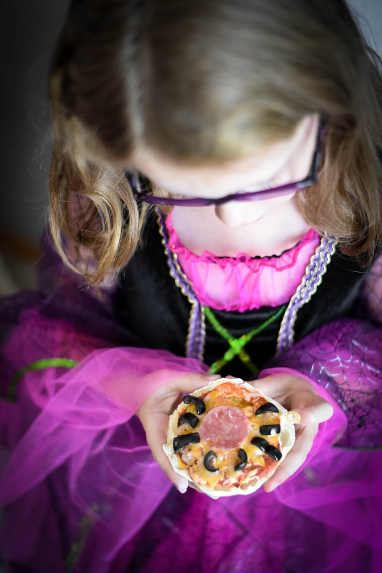 girl dressed as witch holding halloween pizza