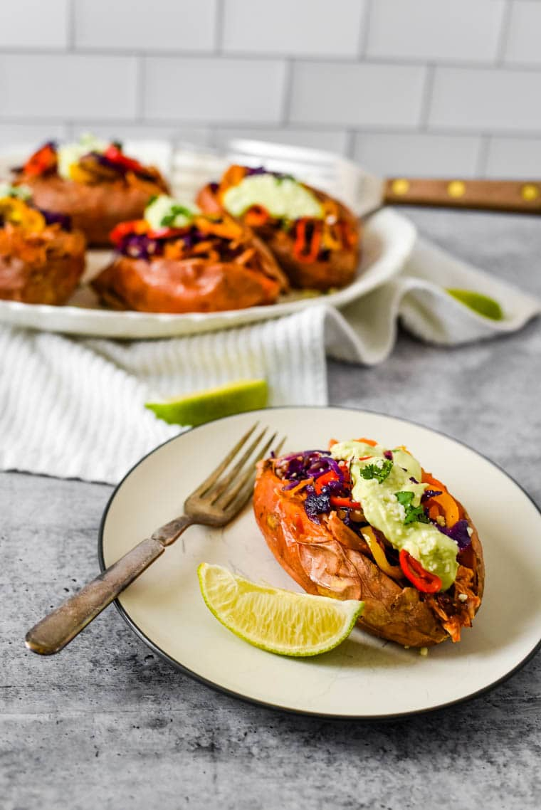 stuffed sweet potato on plate with fork and lime wedge in front of platter of stuffed sweet potatoes