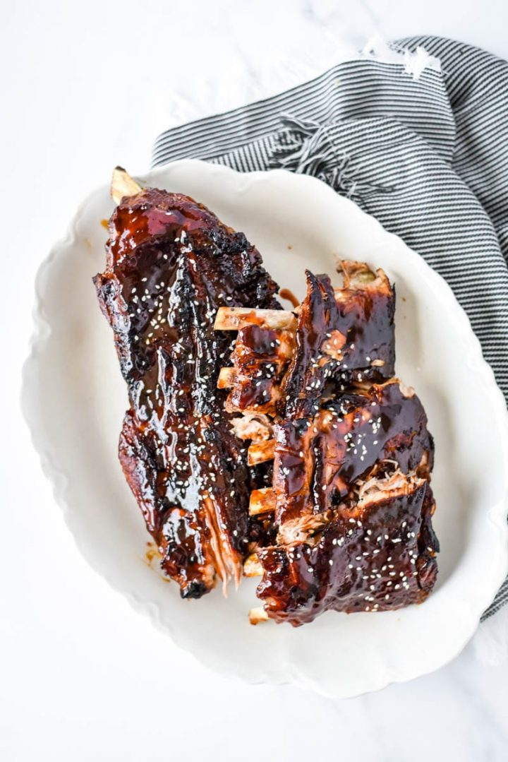 asian sticky ribs on white platter with napkin