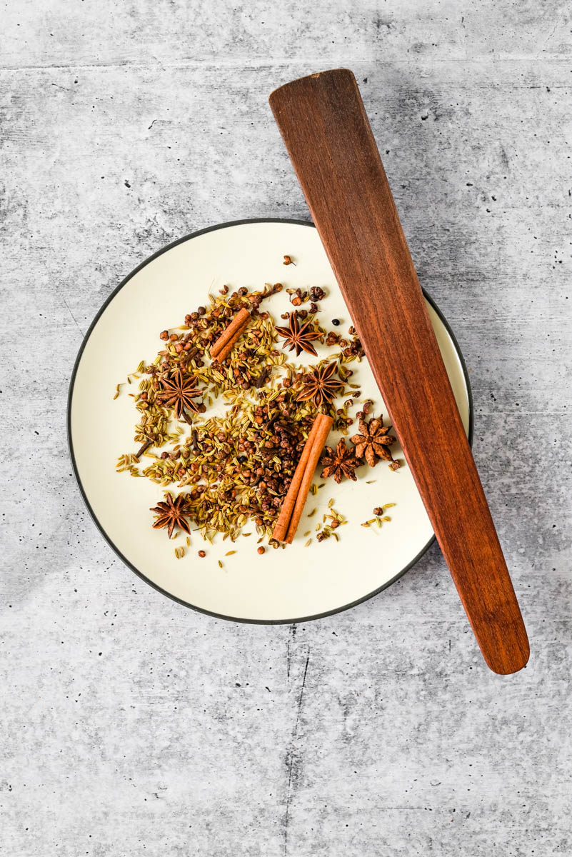 spices for chinese five spice blend on plate with wooden spatula