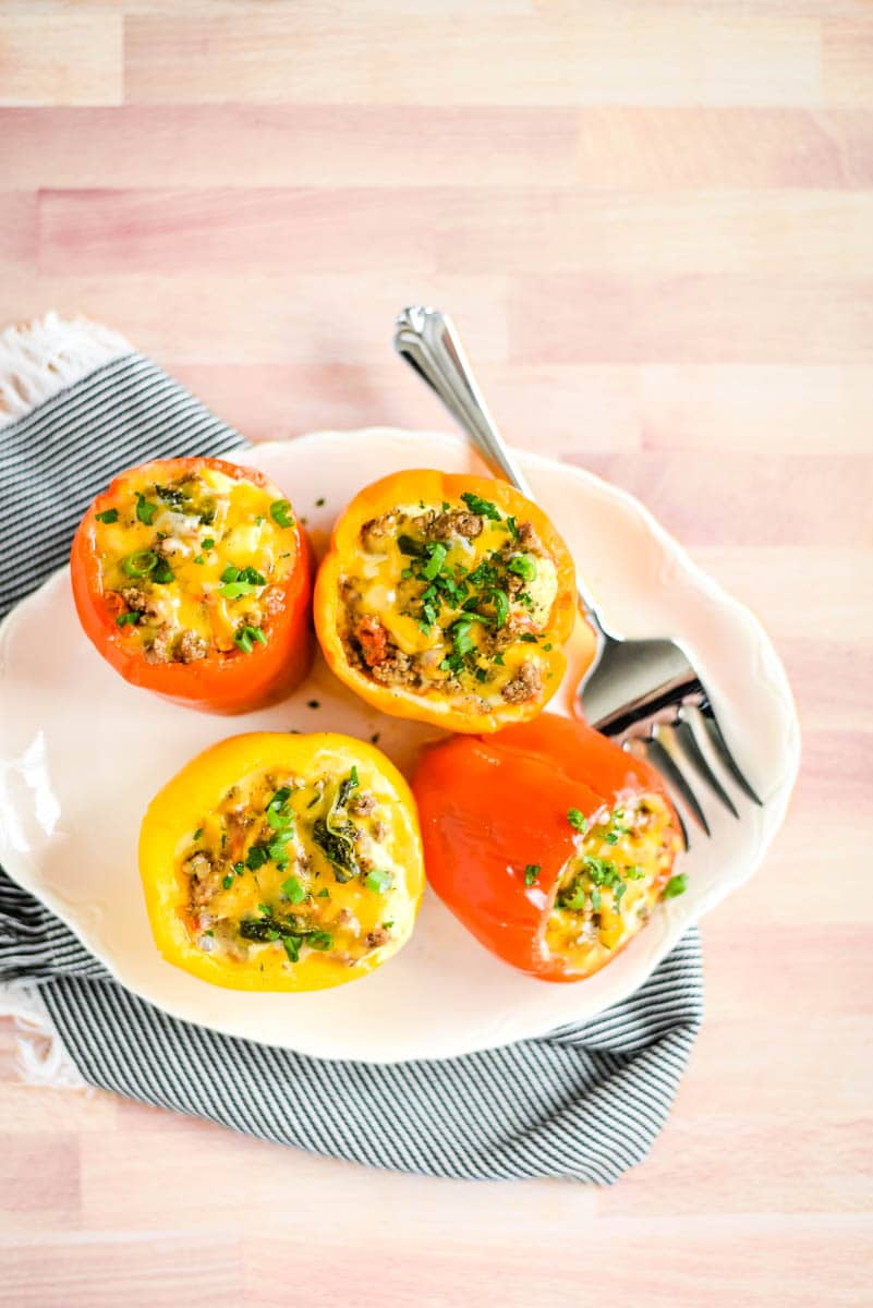 Breakfast stuffed peppers on white plate with napkin