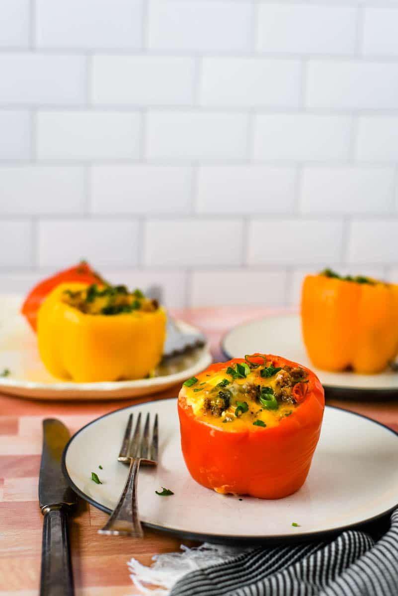 white plates with three breakfast stuffed peppers