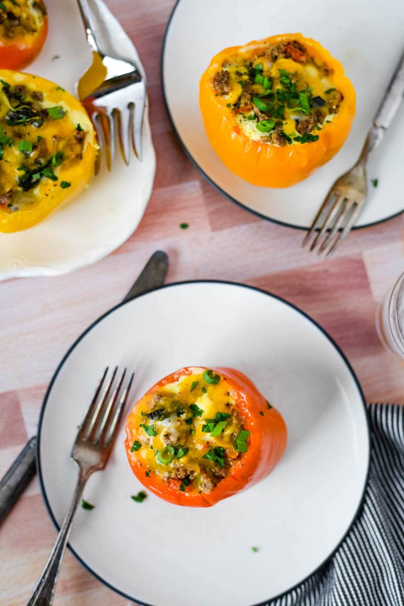 three white plates with breakfast stuffed peppers and silverware