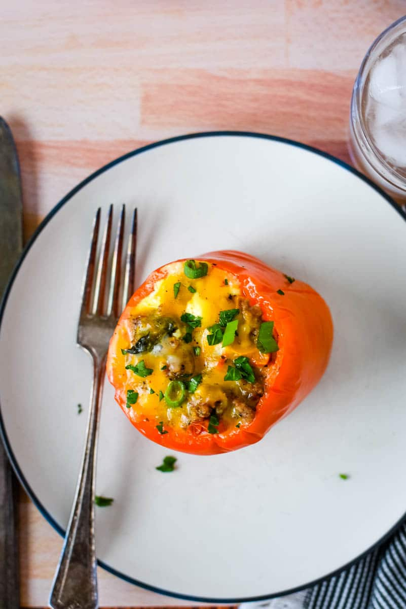 egg stuffed pepper on white plate with fork