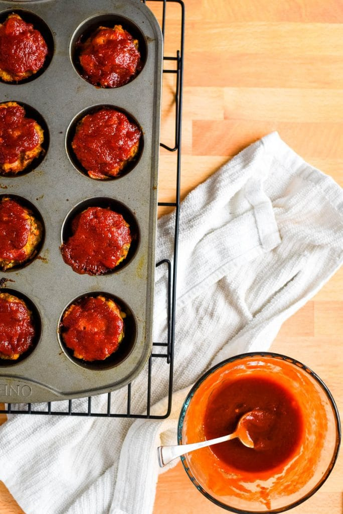 freshly baked turkey meatloaf muffins in tray with dipping sauce beside