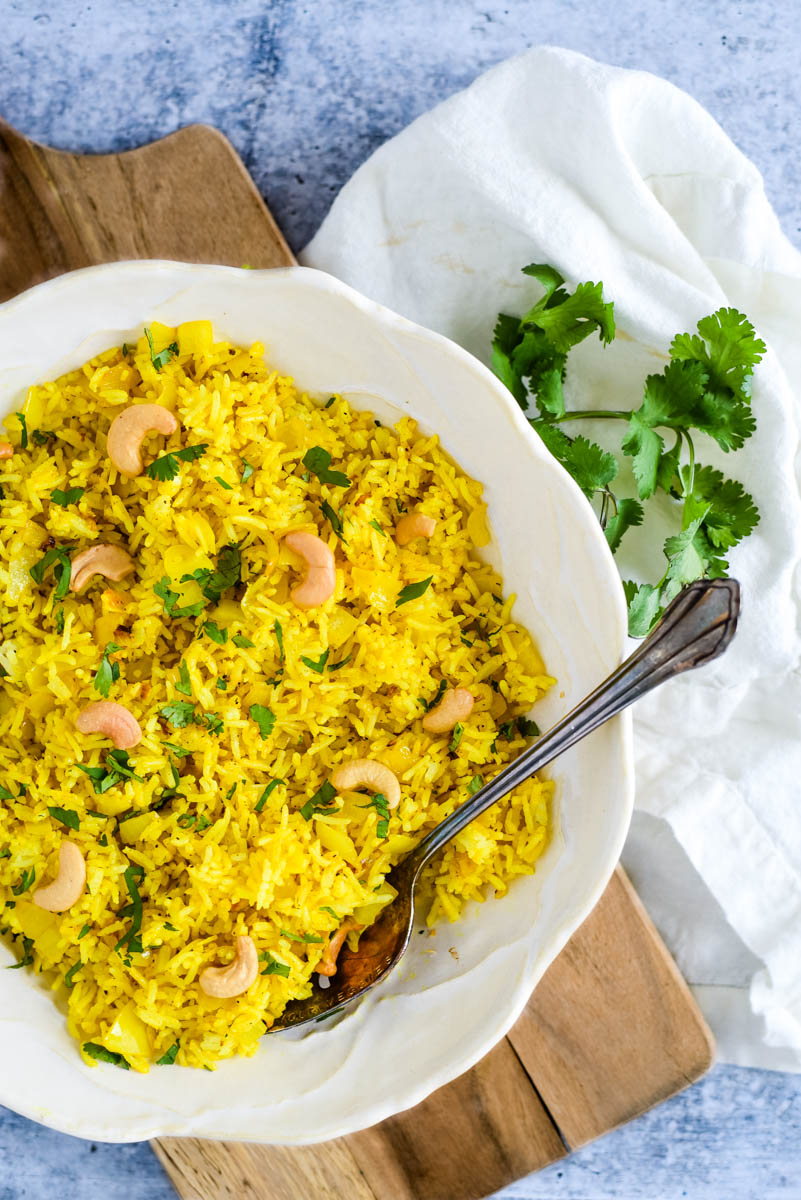 white bowl on wooden board filled with indian lemon rice