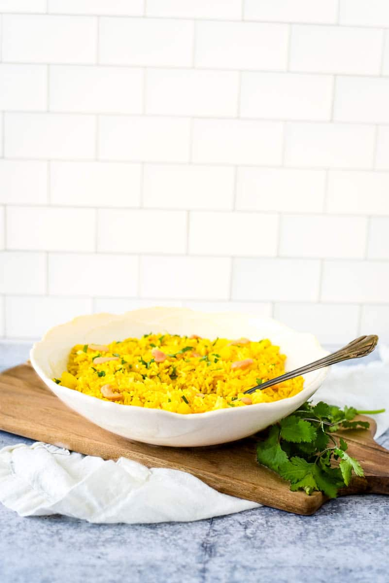 lemon rice recipe in white bowl with kitchen background