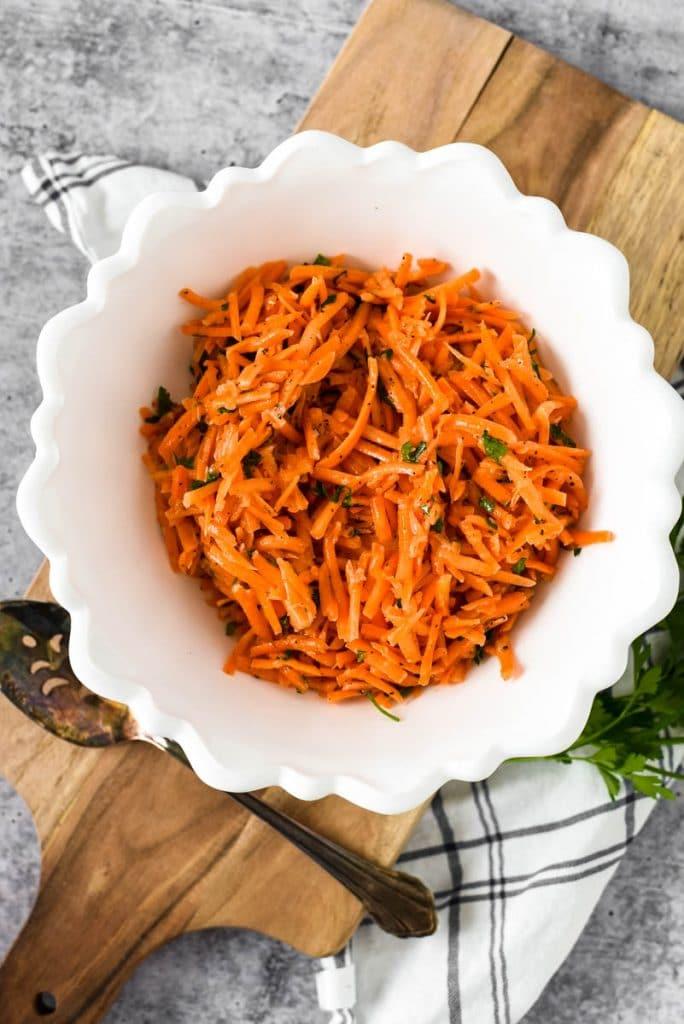 white bowl with shredded carrot salad and lemon dijon vinaigrette dressing