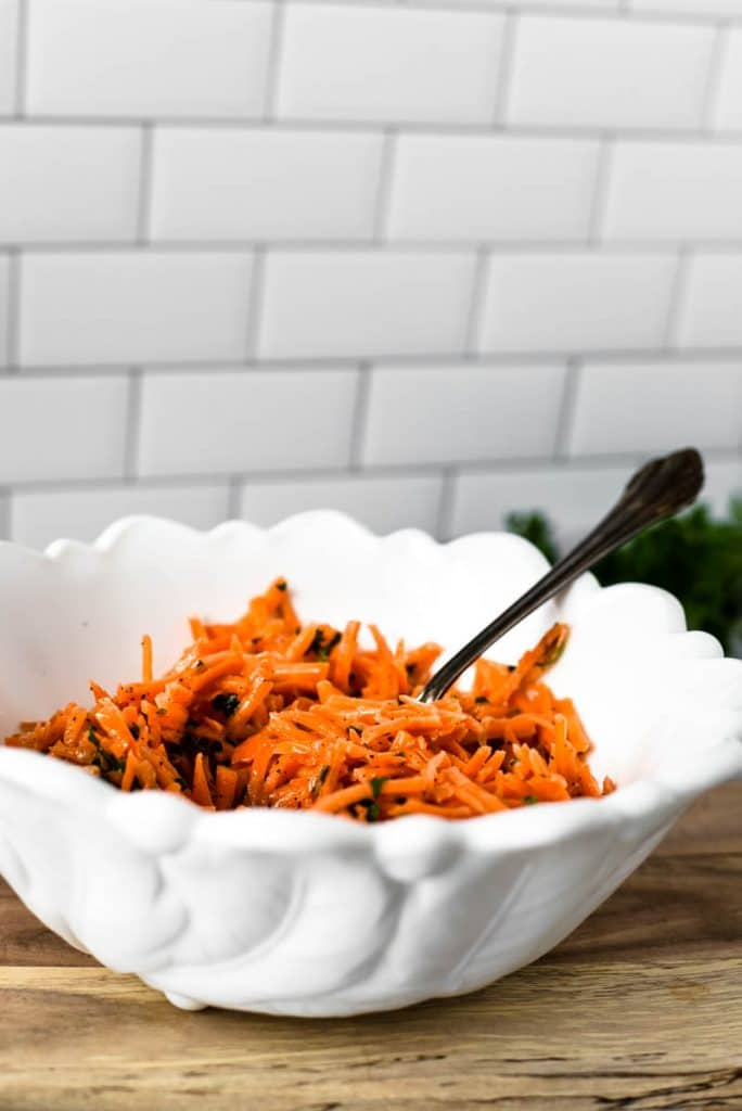 french carrot salad ready to be served in white bowl with spoon