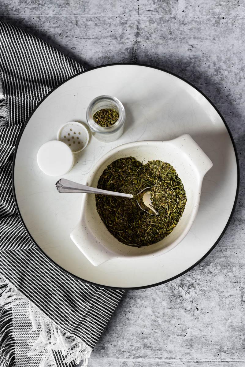 freshly made Italian Herb Seasoning being placed into storage jar